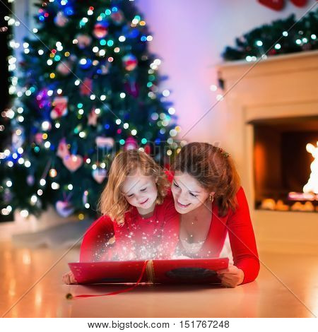 Mother and daughter read a book at fireplace on Christmas eve. Family with child celebrating Xmas. Decorated living room with tree fire place and candles. Winter evening at home for parents and kids.