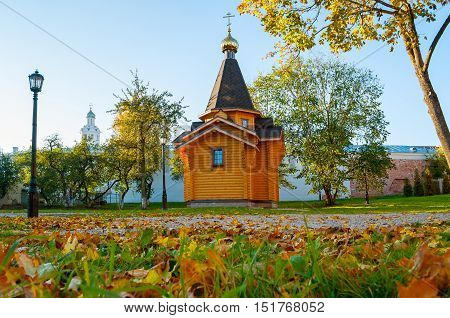 Chapel of St Vladimir - Prince of Novgorod and baptist of Rus in Kremlin in Veliky Novgorod Russia and clock tower of St Sophia Cathedral on the background. Autumn architecture landscape