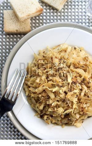 Top view on fried cabbage with caraway and garlic on a plate