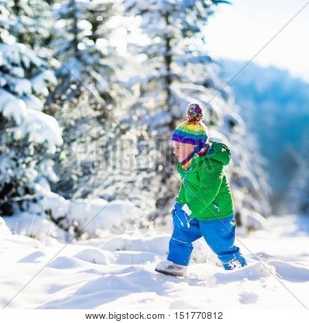Child running in snowy forest. Toddler kid playing outdoors. Kids play in snow. Christmas vacation in sunny winter park for family with young children. Little boy in colorful jacket and knitted hat.