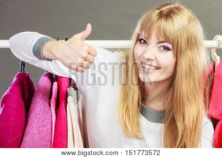 Pretty happy woman with clothing from wardrobe. Young undecided shopper girl bought new clothes. Shopping sale and thumb up gesture concept.