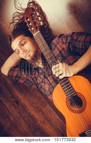 Sleeping man with guitar. Lying on the floor and enjoying the moment.