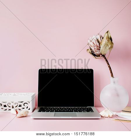 Laptop with black screen on table with proteus flower and decoration