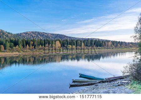 Beautiful autumn day on the tranquil river. Wooden boats moored to the bank of the river. Beautiful river landscape.
