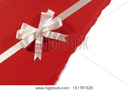 Gift Ribbon And Bow In White Satin On Untidy Torn Red Paper Background