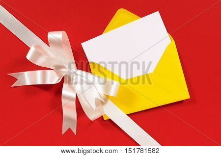 Christmas Card With Diagonal Gift Ribbon And Bow In White Satin On Red Paper Background With Yellow