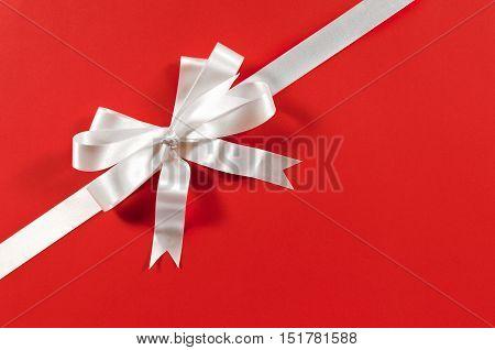 Christmas Border Frame Gift Ribbon In White Satin On Red Paper Background Diagonal