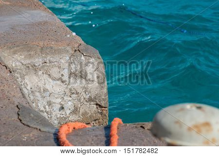 Photo of beautiful clear turquoise sea ocean water surface with ripples and bright splash on stone seascape background. Orange rope at pier.