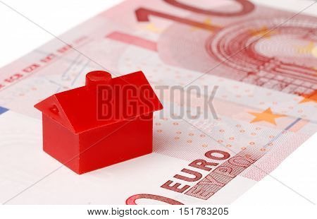 Red litle plastic house on a ten euro banknote on white background.