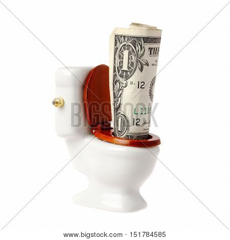 One US dollar banknote in a miniature toilet isolated on white background.