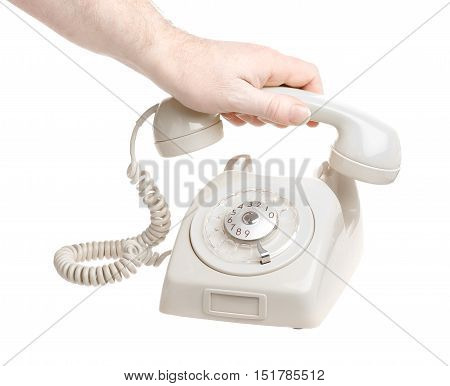 A human holding the reciver of an old Swedish grey telephone with dial isolated on white background.