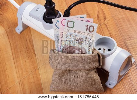 Electrical extension with connected plug and polish currency money in jute bag concept of saving money on electricity energy costs