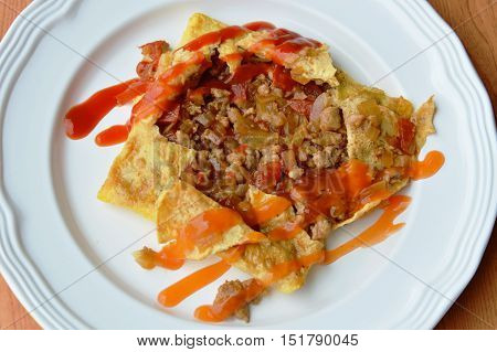stuffed omelet with onion and minced pork dressing sauce on plate