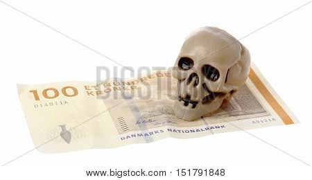 One small plastic skull on Danish 100 kroner banknote isolated on white background.