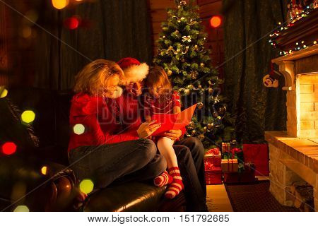 Family read stories at Christmas time sitting on sofa in front of fire place