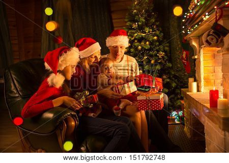 Family exchanging gifts sitting in front of fireplace at Christmas tree