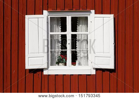 Red painted wooden wall of the house with closed windows that have opened white shutters.