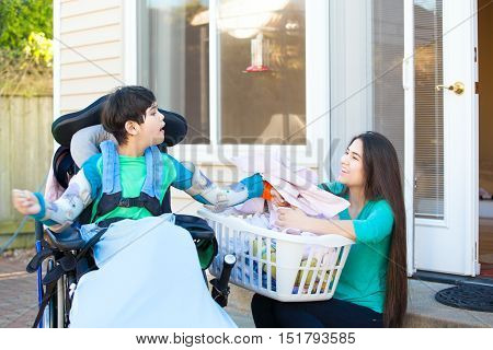 Disabled biracial ten year old boy in wheelchair helping older sister fold laundry on patio outdoors