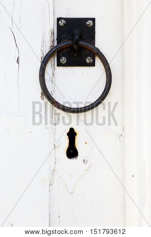 Close up of black handle and keyhole on a white door.