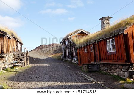 Old wooden buildings with thatched roofs adjacent to the slag heap in the mining town of Roros in Norway.
