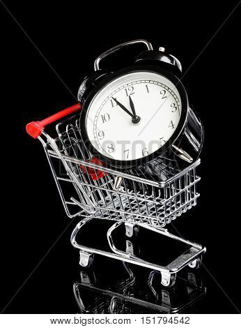 An black alarm clock in a small shopping trolley display time is five to twelve isolated on black.