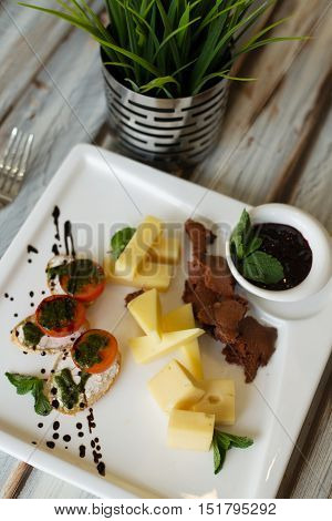Cheese and tomato appetizer or cold collation with green leaves and sauce on a wooden table