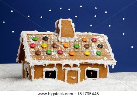 Gingerbread house surronded by winter snow with a blue background with stars