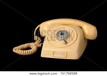 Yellow old Swedish 1960s telephone on hook with dial on black background.
