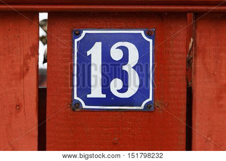 House number thirteen on blue background mounted on red wooden fence.