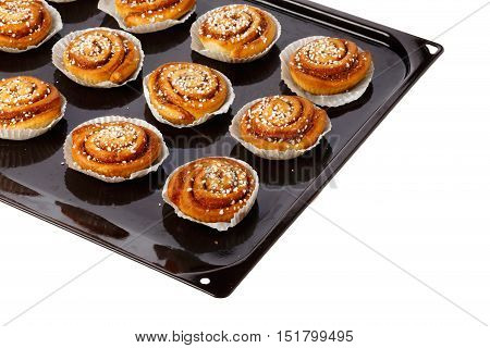 Cinnamon buns in tins of greaseproof paper on a baking tray on white.