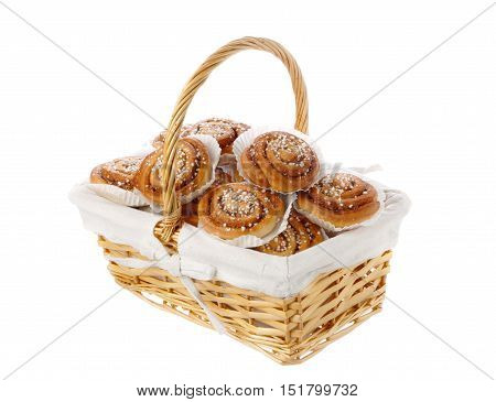 Wicker basket filled with cinnamon rolls in tins of greaseproof paper isolated on white.