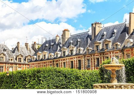 Historic buildings with fountain at the famous Place des Vosges in Paris