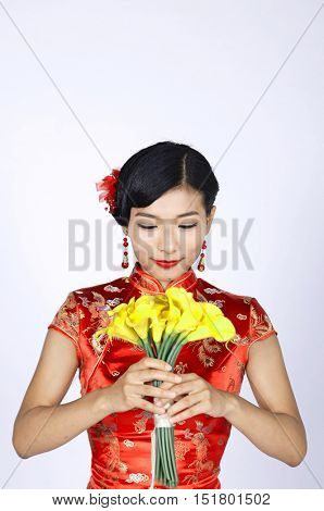 pretty chinese young woman holding a bunch of yellow daffodils