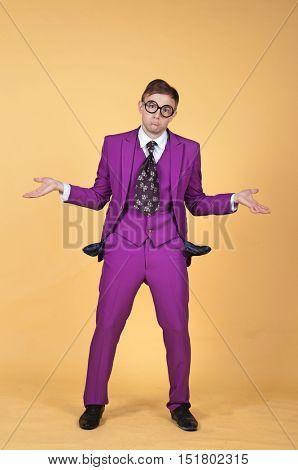 Broke caucasian handsome geek nerd smart clothes with no money in studio with yellow background