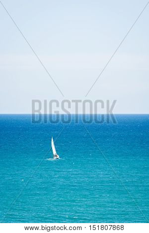 A yacht alone sailing by sea on a clear day