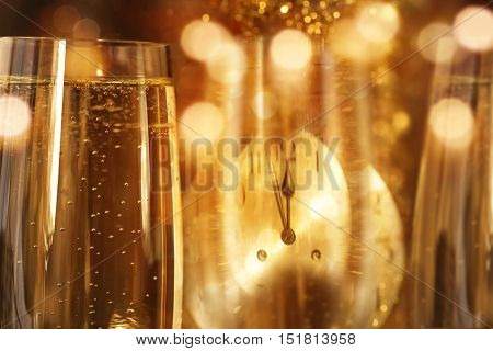New year background with a glass champagne and a clock face