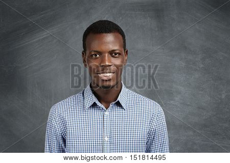 Portrait Of Attractive Dark-skinned Student Wearing Checkered Shirt Looking At Camera With Confident