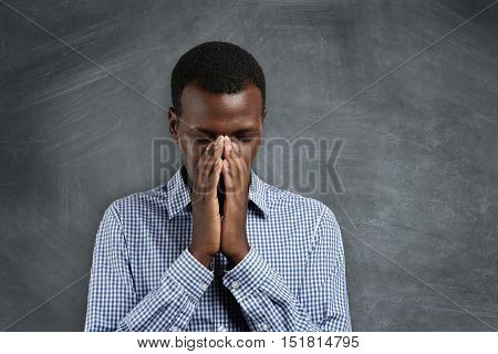 Young African Man Holding Hands In Prayer, Trying To Calm Down , Thinking Of Something Bad, Hoping F