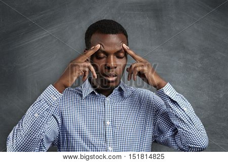 Handsome Serious Puzzled African Student Dressed In Checkered Shirt Robbing His Forehead, Closing Hi