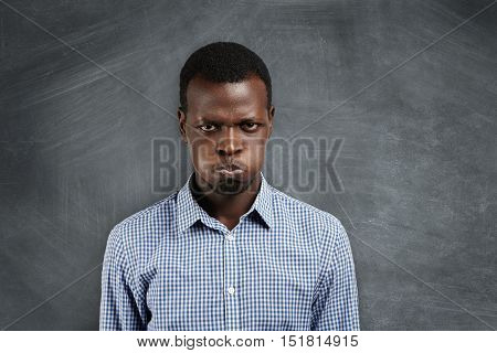 Portrait Of Irritated Young Dark-skinned Teacher Looking With Grumpy And Angry Expression, Blowing H