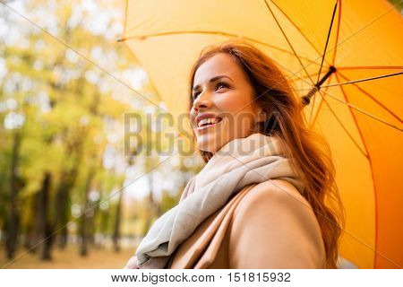 season, weather and people concept - beautiful happy young woman with yellow umbrella walking in autumn park