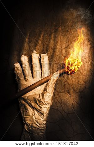 Hand of a historic horror mummy holding a torch flame in a dark cursed tomb. Rise of the dead mummy