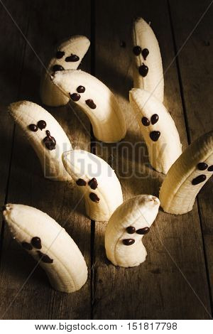 Dark food art on crafty ghost bananas with melted chocolate eyes on wooden planks. Sliced halloween fun