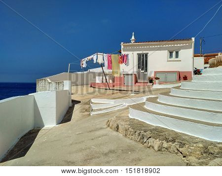 House and wall above the ocean on coastline of Peniche, Portugal