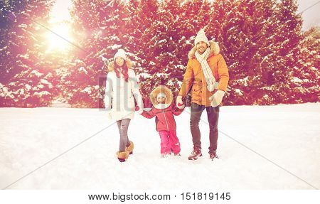 parenthood, fashion, season and people concept - happy family with child in winter clothes walking outdoors