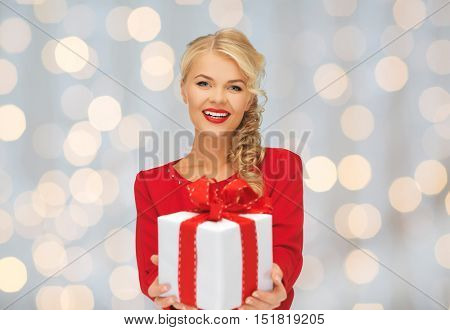 christmas, holidays, valentines day, birthday and people concept - happy smiling woman in red dress with gift box over lights background