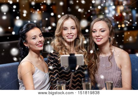 celebration, friends, bachelorette party, technology and christmas holidays concept - happy women with champagne and smartphone selfie stick taking picture at night club over snow