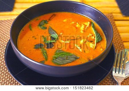 red curry spicy chicken soup with grass leaf in bowl on the table