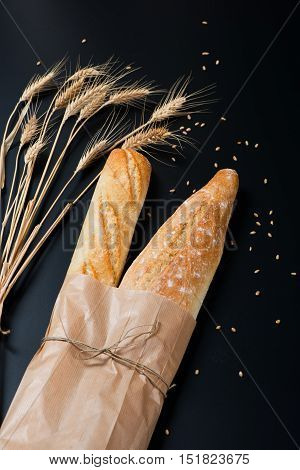 Loaves of french baguette bread tied together with paper and string decorated with wheat ears and cereals on a black background.