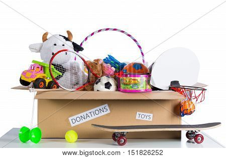 Box of assorted toys to donate with white background
